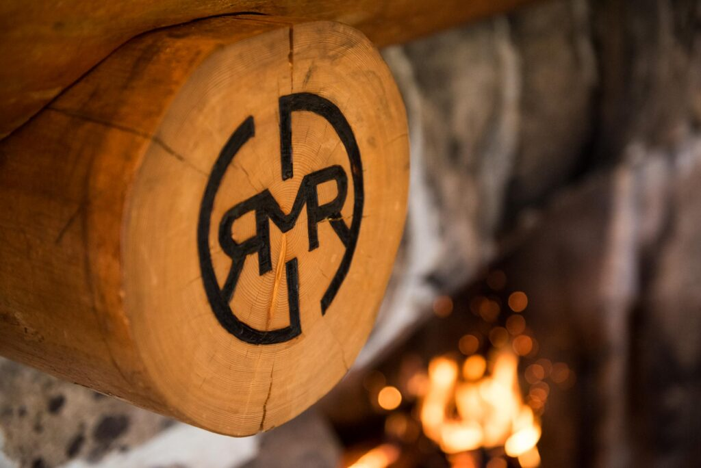 The Idaho Rocky Mountain Ranch logo stamped in the wood beams hanging over a nice cozy fireplace