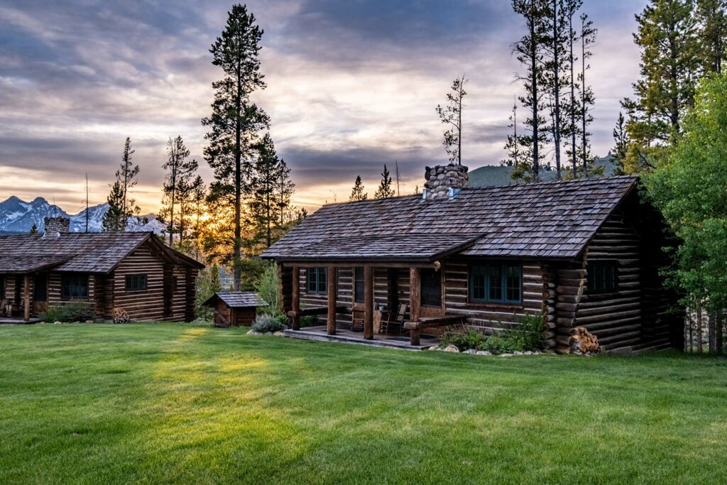 Our beautiful rocky mountain comfort cabins as the sun sets behind the snow capped sawtooth mountains