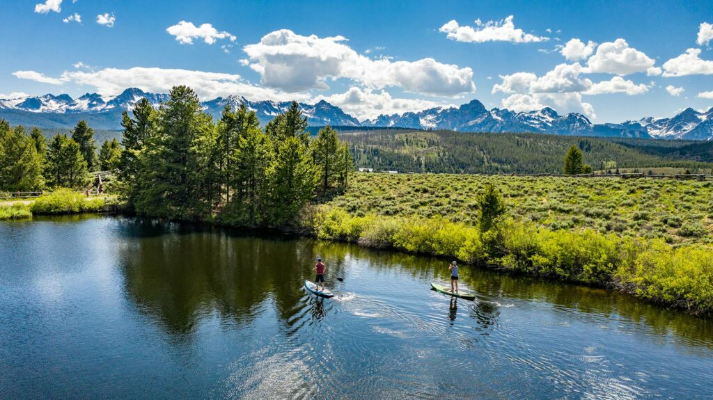 Stand up paddle boarding on a lake or river near the rocky mountain in stanley idaho