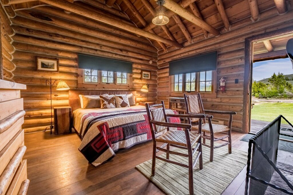 A relaxing master bedroom in a log cabin with a private entrance overlooking the sawtooth mountains in stanley idaho