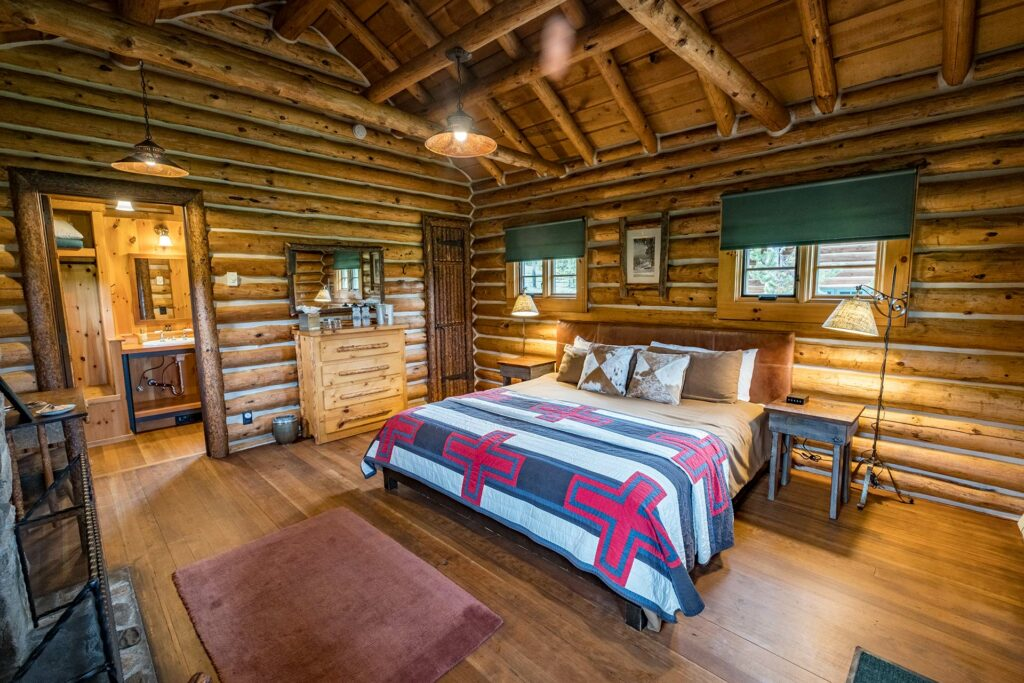 A cozy master bedroom including a fire place and private bathroom in our family log cabin at our idaho guest ranch