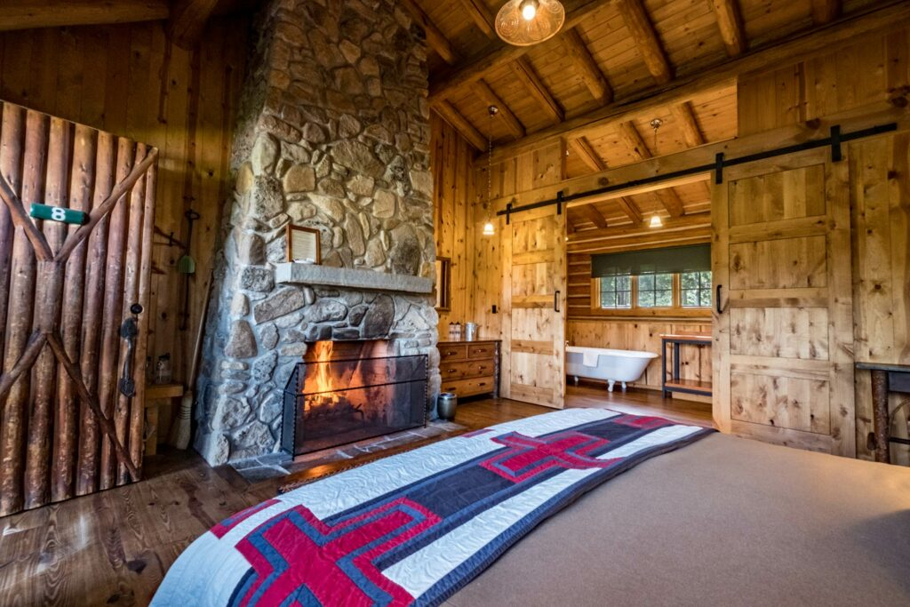 A cozy master bedroom including a cozy fire place and private bathroom in our family log cabin at our idaho guest ranch