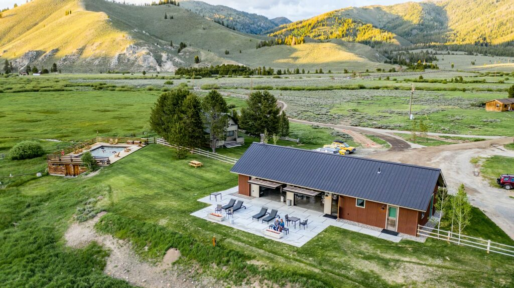 An overhead view of the idaho rocky mountain ranch lodge with our private rocky mountain hot springs in a beautiful green valley