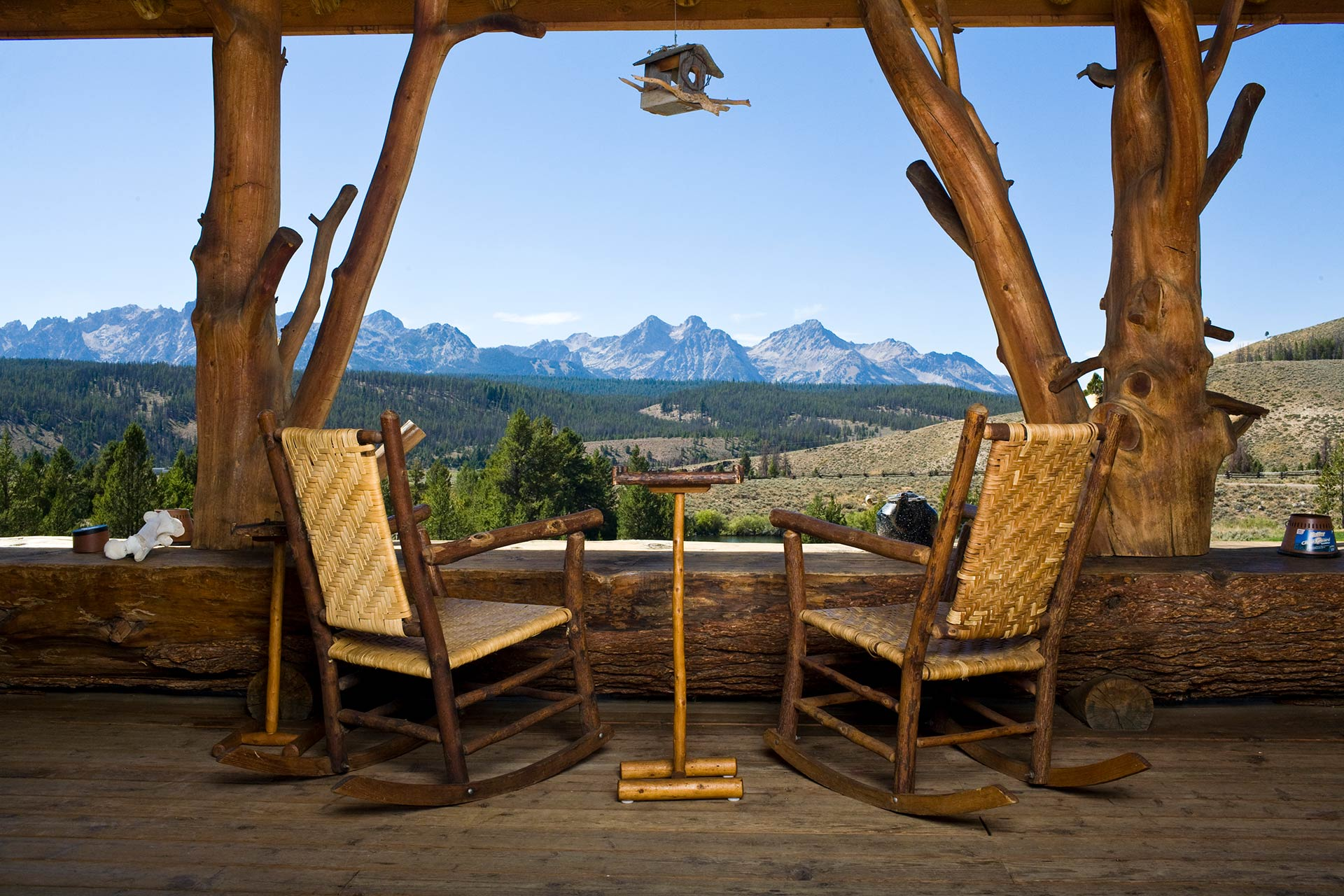 Relaxing on the porch overlooking a forest and the sawtooth mountains at a rocky mountain lodge and cabins